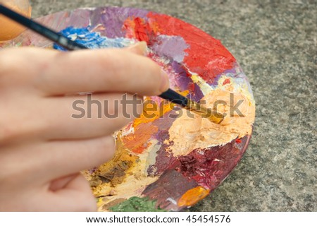 hand holding paintbrush and mixing oil-paint on palette