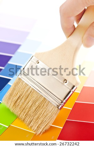 Hand holding paintbrush over color card samples - stock photo
