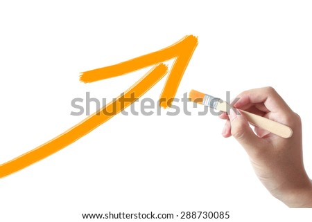 Hand holding painting brush is drawing Growth arrow on white background. - stock photo