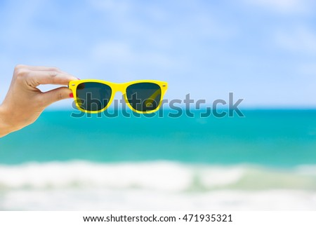 Hand holding pair of sunglasses on the beach.