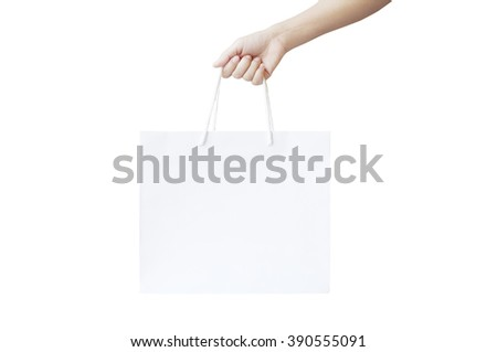 Hand holding paper bag on white background - stock photo