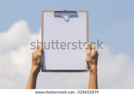 Hand holding paper board up to the sky. Concept for success or other message. - stock photo
