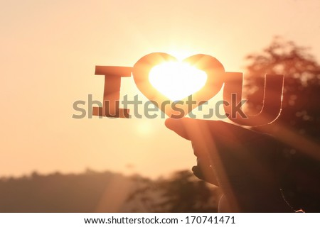 hand holding paper cut i love you of lovers on the background of sunset  - stock photo