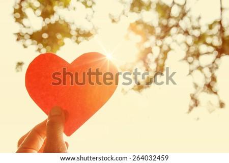 Hand holding paper heart.  Instagram effect.  - stock photo