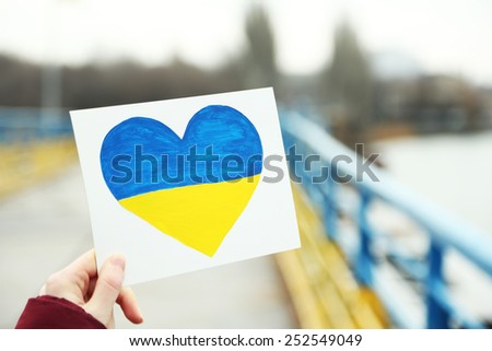 Hand holding paper heart with painted Ukraine flag  - stock photo