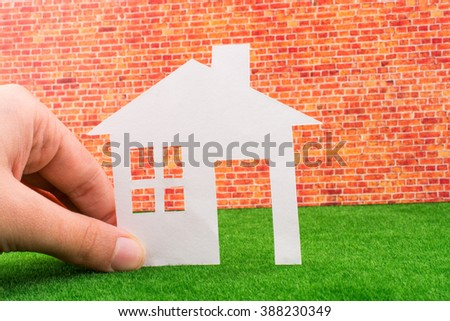 Hand holding Paper House on red brick background