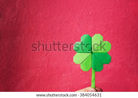 Hand holding paper origami green shamrock on pink wall background. Space for copy, lettering, text. St. Patrick's day postcard template. - stock photo
