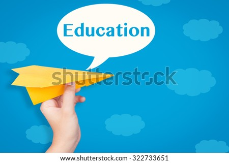 hand holding paper plane with education in speech bubble on blue background  - stock photo