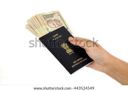 Hand holding passport with Indian currency
