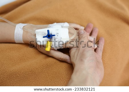 Hand holding patient hand in the hospital - stock photo