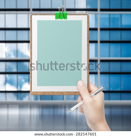 hand holding pen and green blank clipboard with office building background - stock photo