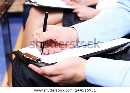 Hand holding pen and making notes at conference