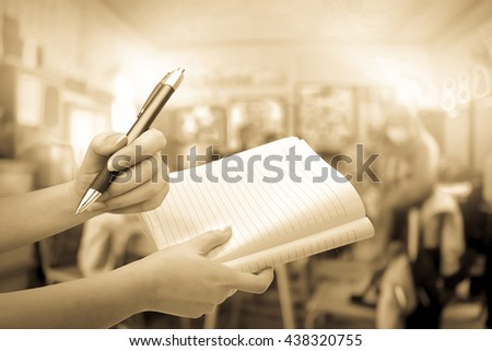 hand holding pen and notebook with blur student in classroom background - stock photo