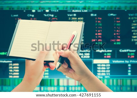 hand holding pen and notepad with blur graph stock market background