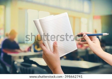 hand holding pen and notepad with blur student in classroom background - stock photo