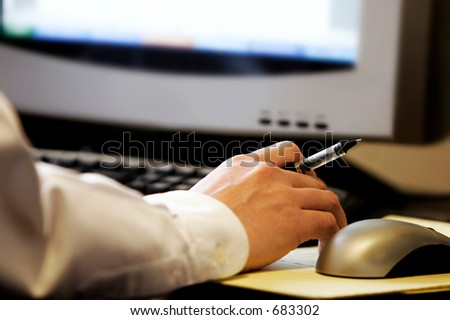 Hand holding pen in front of  computer screen, with mouse and keyboard - represents computer work and research. - stock photo
