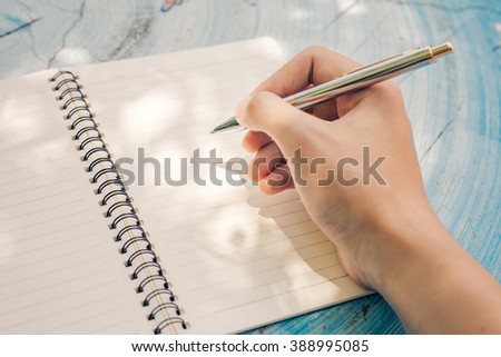 hand holding pen on notebook. - stock photo