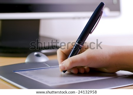 Hand holding pen on  tablet