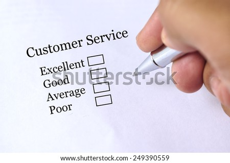 "Hand Holding Pen to Rate ""CUSTOMER SERVICE"" Survey, Selective Focus"