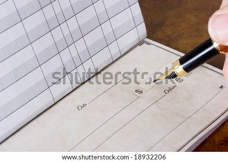 Hand holding pen writing in chequebook sitting on table, paying the bills - stock photo