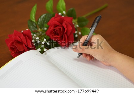 hand holding pen writing on notebook with rose