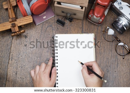 Hand holding pencil and white blank paper notebook on wooden table. Travel preparing concept. - stock photo