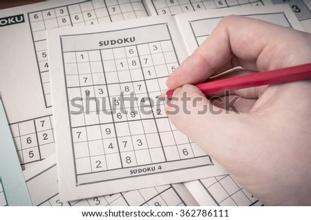 Hand holding pencil is solving sudoku crossword. - stock photo