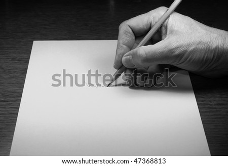 Hand holding pencil on paper - stock photo