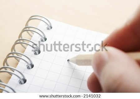 Hand holding pencil on the cross-ruled paper - stock photo