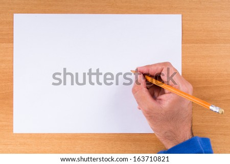 Hand holding pencil on white, blank paper on wood background. - stock photo