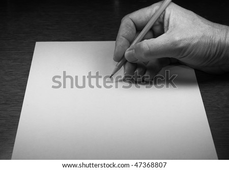 Hand holding pencil over paper - stock photo