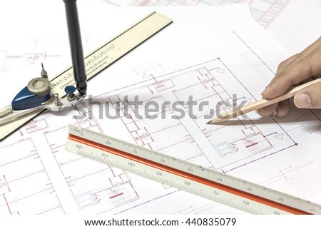 hand holding pencil point to architectural plans project drawing, architect engineering and contractor concept - stock photo