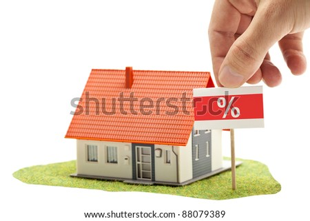 Hand holding percent-sign in front of model house - real estate discount concept - stock photo