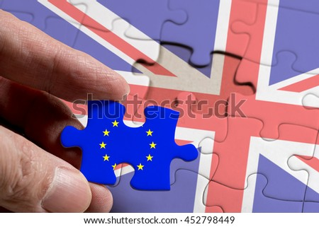 Hand holding piece of jigsaw puzzle with flag of European Union and Great Britain. BREXIT of Great Britain concept.