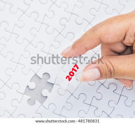Hand holding piece of jigsaw puzzle with 2017 word piece. Concept with year 2017.