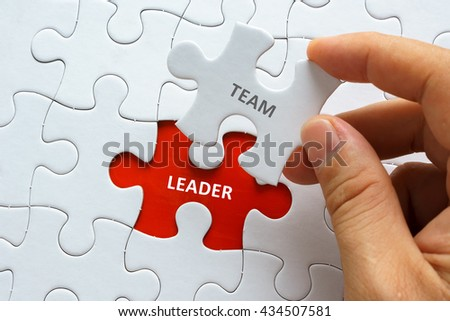 Hand holding piece of jigsaw puzzle with word TEAM LEADER. - stock photo