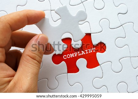 Hand holding piece of puzzle with word COMPLAINT