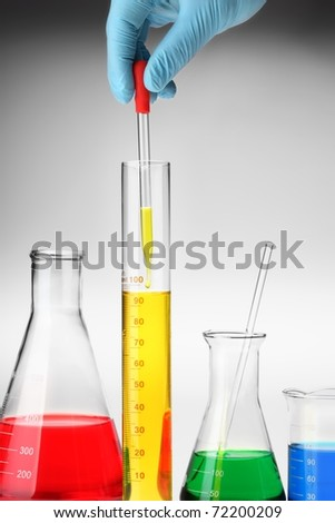 hand holding Pipette with emerging drop of liquid over graduated cylinder. - stock photo