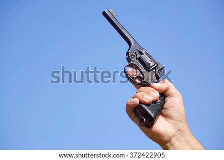 Hand holding pistol firearm pointing up with blue sky background. The pistol is used in sports. - stock photo