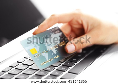 Hand holding plastic credit card and using laptop. Online shopping concept. - stock photo