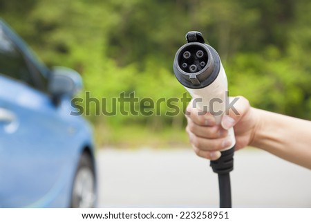 hand holding plug in connector for Charging electric car. eco energy concept - stock photo