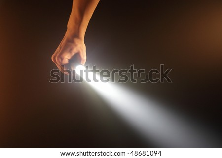 hand holding pocket flashlight - stock photo