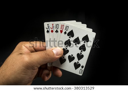 Hand holding poker cards to form a full on black background - stock photo