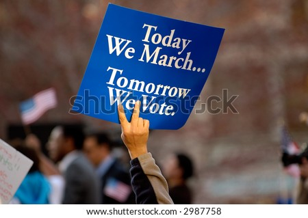 Hand holding political sign at pro immigration rally - stock photo