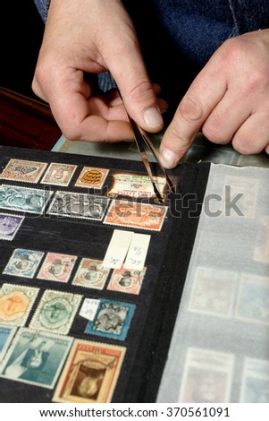 Hand holding postage stamp with tweezers over album