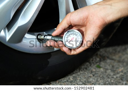 Hand holding pressure gauge for car tyre pressure measurement - stock photo
