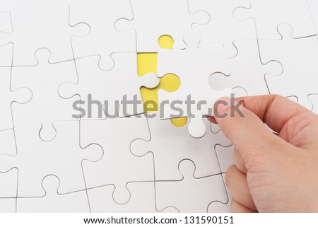 Hand holding puzzle piece and inserting it into group of white paper jigsaw puzzles