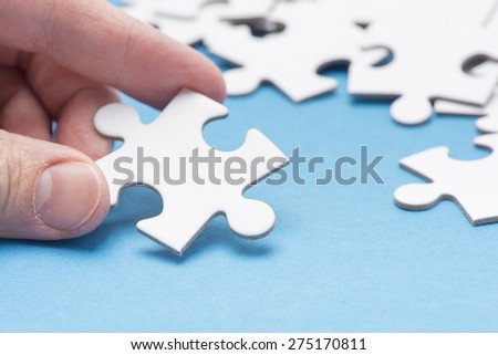 Hand holding puzzle piece. Conceptual image of connection, solution and business strategy. - stock photo
