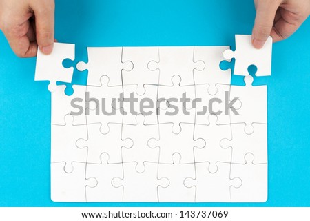 Hand holding puzzle pieces and inserting them into group of white paper jigsaw puzzles - stock photo