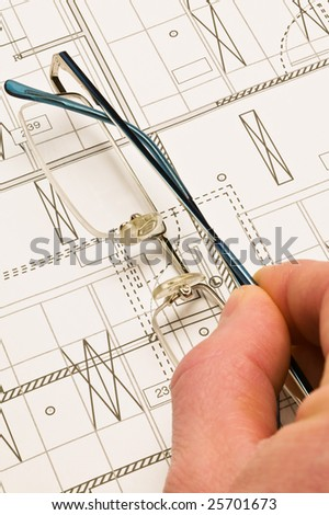 Hand holding reading glasses on a blueprint
